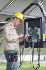 Technicians Working Under Solar Panels