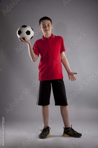 Boy with soccer ball posing in studio