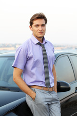 Handsome man standing near car