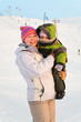 Mother and her little child standing on winter ski mountain