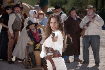 Defiant cowgirl pointing gun.