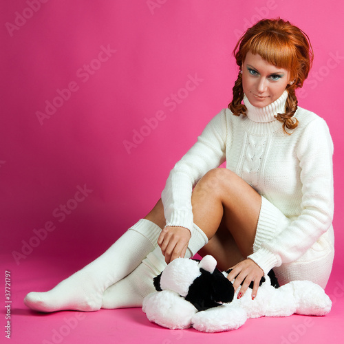 Portrait of a red-haired girl in a white sweater with a soft toy