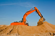 Excavator working at sandpit moving earth by its bucket