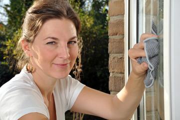 Junge Frau putzt Fenster