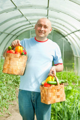 man with baskets of   vegetables
