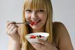 Junge hübsche Frau isst Obstsalat