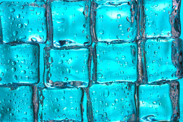 Melting ice cubes on blue closeup