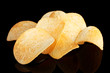 Delicious potato chips on black background