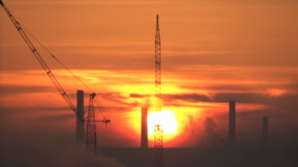 cranes and industry in a morning sunrise