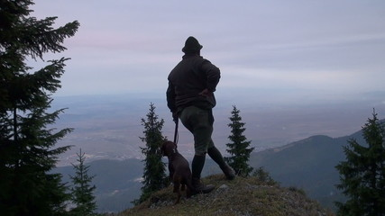 hunter with his dog on a rock