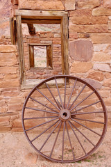 A wheel in front of historic building at Lees Ferry