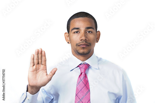 Hispanic man taking oath or pledge hand raised