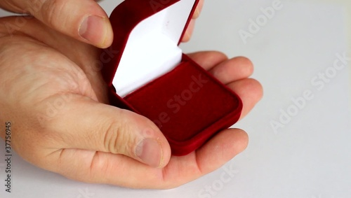 Opened red jewelry box to putting rings.