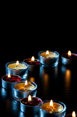 Semicircle of tea light candles burning in the dark