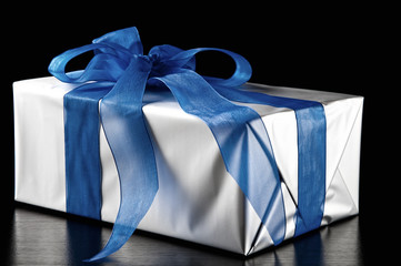 Silver gift box with blue ribbon, black background