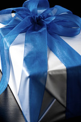 Close-up of gift wrapped with blue bow, close-up