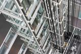 Looking down in  an open steel lift shaft in a modern buldin poster