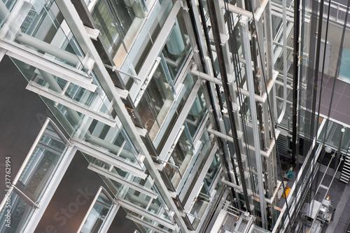 Looking down in  an open steel lift shaft in a modern buldin
