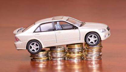 Model car on a pile of coins on the table