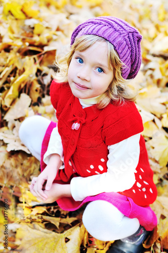little blonde girl sitting in foliage