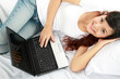 girl lying in bed with laptop