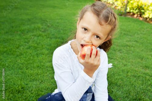 Девочка ест красное яблоко - 37768194