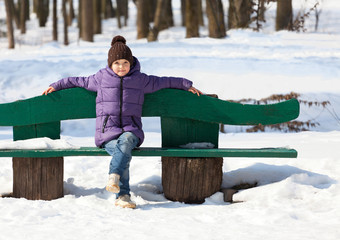 7 year old girl on a bench in winter park