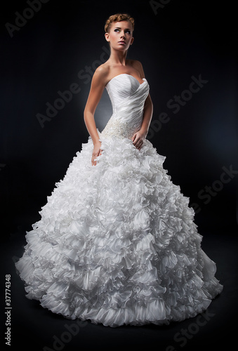 Pretty bride in white nuptial dress posing in studio