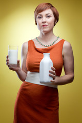 Woman holding glass of milk and bottle