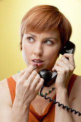 Woman applying lipstick while using a rotary telephone