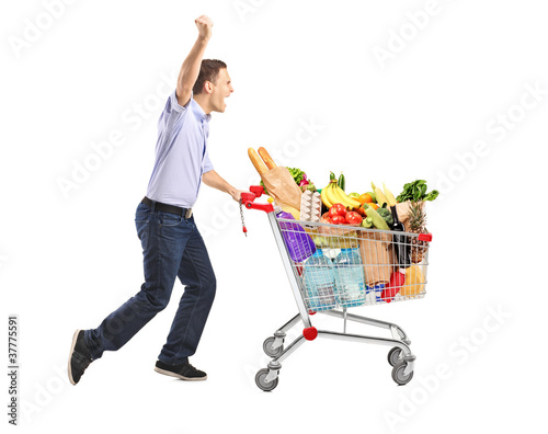 Euphoric man pushing a shopping cart full with food