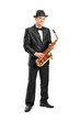 Full length portrait of a man in a suit holding a saxophone