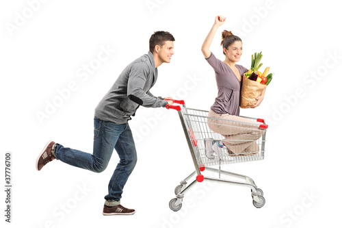 Person pushing a happy woman in a shopping cart with paper bag f