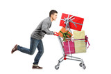 Young man running and pushing a shopping cart with gifts