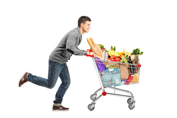 Young man running and pushing a shopping cart full with food