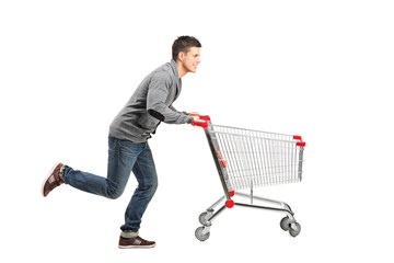 Young man running and pushing an empty shopping cart