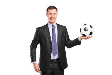 Young smiling businessman holding a football