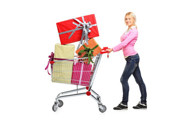 Young woman pushing a shopping cart full with gifts