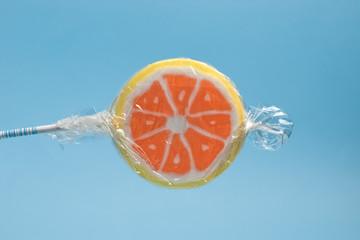 wrapped orange lollipop on a stick against blue