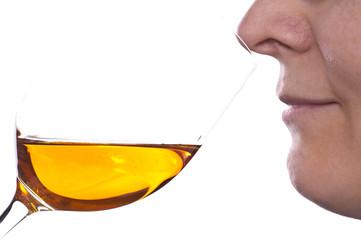 Frau tut Wein am Weinglas riechen