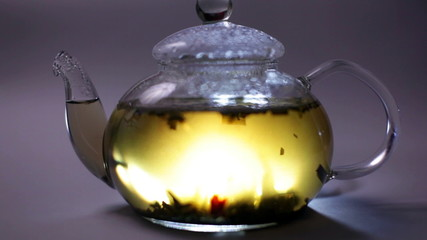 Glass teapot with a tea leaf in  , illumination