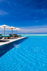 Deck chairs and infinity pool over amazing lagoon