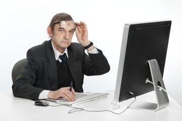 Пожилой мужчина работает за компьютером.