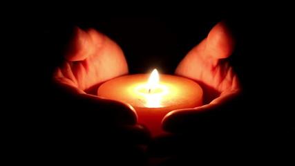 Candle between hands