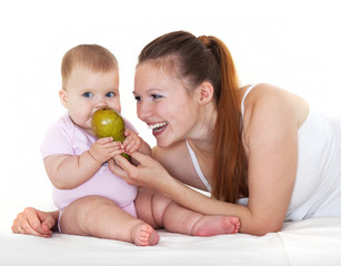 Happy mum feeds with a pear the babe.