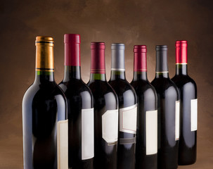 Red wine bottles lined up in a row