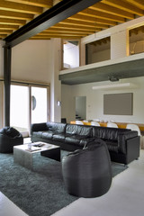 divani di pelle nera in soggiorno e tavolo da pranzo