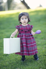 toddler carrying toys in park