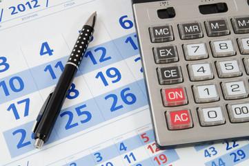 Calculator and black pen on calendar