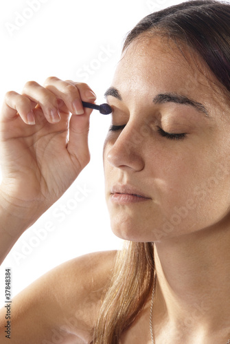 Woman putting on make-up cosmetic's eye shadow.